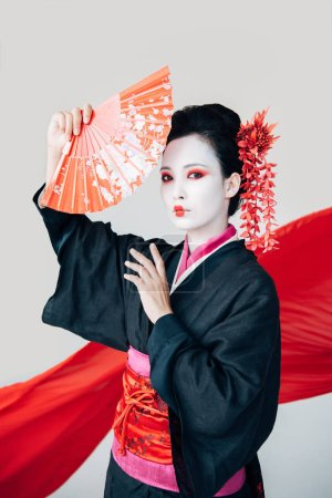 Photo for Beautiful geisha in black kimono posing with hand fan and red cloth on background isolated on white - Royalty Free Image
