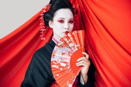 Photo pour Belle geisha dans le kimono noir avec le ventilateur de main et le tissu rouge sur le fond d'isolement sur le blanc - image libre de droit