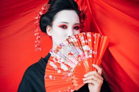 Foto de Hermosa geisha en kimono negro con ventilador de mano y tela roja en el fondo - Imagen libre de derechos