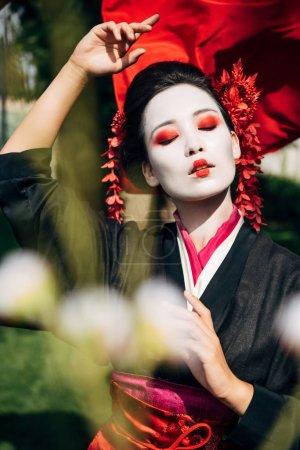 Photo pour Foyer sélectif des branches d'arbres et belle geisha gestuelle avec tissu rouge sur le fond dans la lumière du soleil - image libre de droit