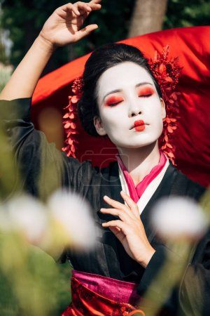 Photo for Selective focus of tree branches and dancing geisha with red cloth on background in sunlight - Royalty Free Image