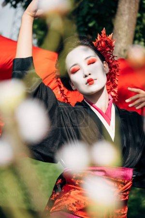 Photo pour Foyer sélectif des branches d'arbre et de belles geisish a dansantes avec le tissu rouge sur le fond dans la lumière du soleil - image libre de droit
