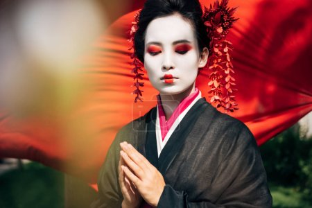 Photo for Selective focus of tree branches and beautiful geisha with greeting gesture and red cloth on background in sunlight - Royalty Free Image