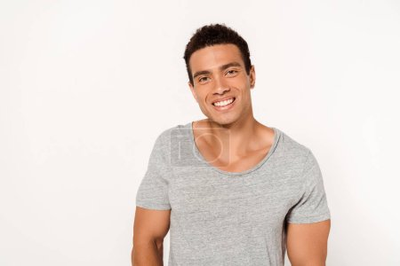 Photo for Happy mixed race man smiling while looking at camera on white - Royalty Free Image