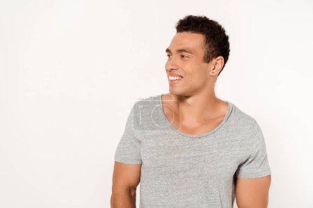 Photo pour Positif homme métis en t-shirt gris souriant sur blanc - image libre de droit