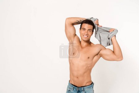 Photo for Happy mixed race man with tattoo undressing and looking at camera on white - Royalty Free Image