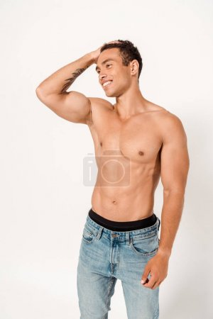Photo for Happy and shirtless mixed race man touching hair while standing on white - Royalty Free Image