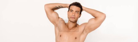 panoramic shot of handsome mixed race man with tattoo looking at camera on white