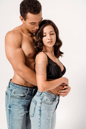 Photo for Sexy mixed race man hugging beautiful girlfriend in lace bra on white - Royalty Free Image