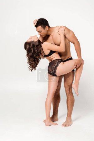 Photo pour Beau homme mélangé de course étreignant la fille gaie dans les sous-vêtements de dentelle sur le blanc - image libre de droit