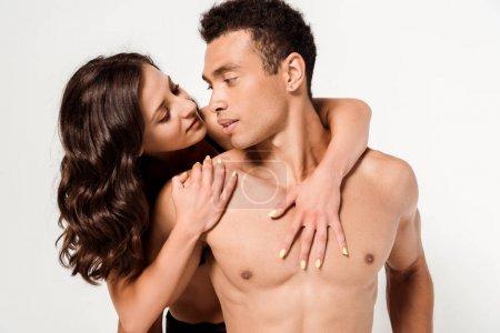 Photo pour Jolie femme étreignant l'homme de course mélangé étreignant la femme sexy d'isolement sur le blanc - image libre de droit