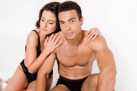 Photo pour Jeune femme dans des sous-vêtements étreignant l'homme mélangé torse nu de course d'isolement sur le blanc - image libre de droit