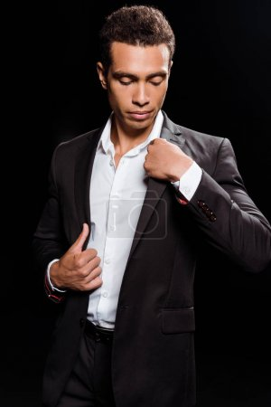 Photo for Handsome bi-racial man looking at formal wear isolated on black - Royalty Free Image