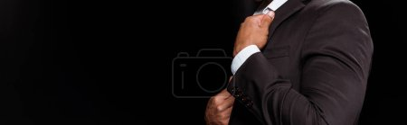 Photo for Panoramic shot of bi-racial man touching formal wear isolated on black - Royalty Free Image