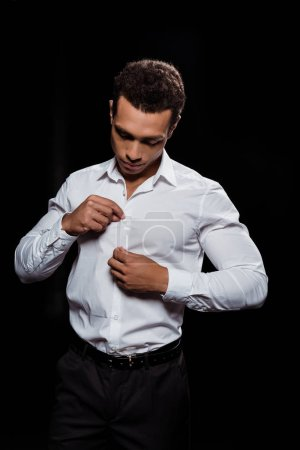 Photo for Handsome bi-racial man touching and looking at white shirt isolated on black - Royalty Free Image