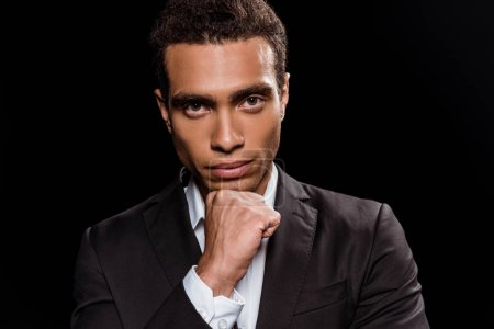 pensive mixed race man looking at camera isolated on black