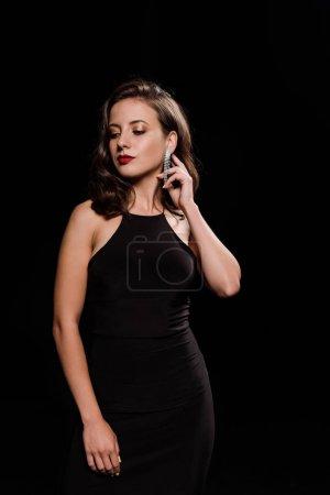 Foto de Elegante joven tocando pendiente aislado en negro - Imagen libre de derechos