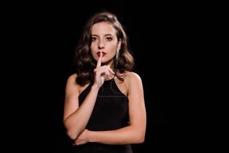 Photo pour Attrayant et élégant femme montrant signe de silence isolé sur noir - image libre de droit