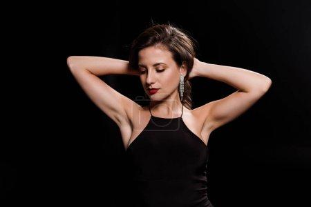 Photo pour Jeune femme toucher les cheveux tout en se tenant en robe isolé sur noir - image libre de droit