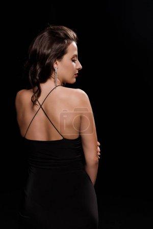 Photo pour Vue de côté de la belle femme dans la robe d'isolement sur le noir - image libre de droit