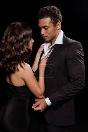 Photo pour Jeune femme touchant cravate de beau mixte homme isolé sur noir - image libre de droit