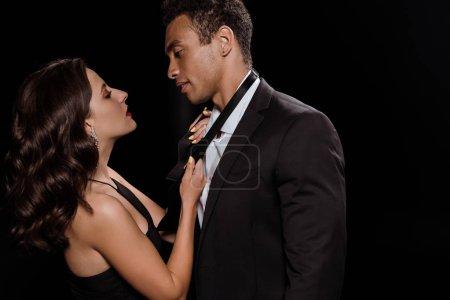Photo pour Femme touchant cravate de beau mixte homme isolé sur noir - image libre de droit