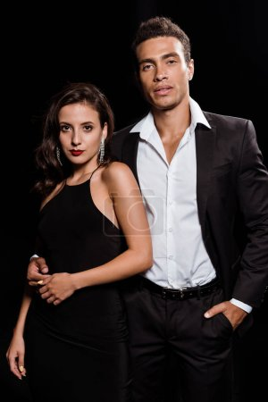 Photo for Handsome mixed race man standing with hand in pocket near attractive woman isolated on black - Royalty Free Image