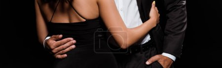 Photo for Panoramic shot of young woman hugging man standing with hand in pocket isolated on black - Royalty Free Image