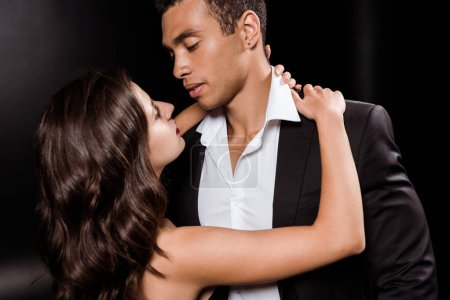 Photo for Young woman hugging handsome mixed race man isolated on black - Royalty Free Image