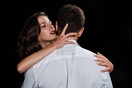 Photo pour Vue arrière de l'homme restant près de la fille attirante d'isolement sur le noir - image libre de droit