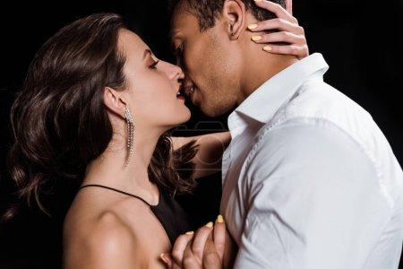 Photo pour Jeune femme attirante embrassant avec l'homme mélangé de course d'isolement sur le noir - image libre de droit