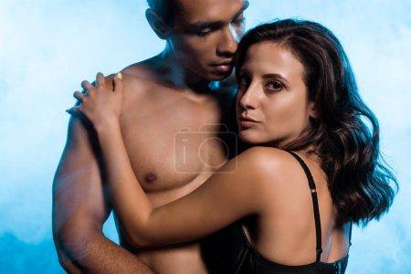 Photo pour Homme mélangé torse nu de course regardant la femme sensuelle dans le soutien-gorge sur le bleu avec la fumée - image libre de droit