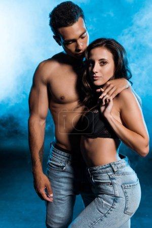 Photo pour Homme de race mixte torse nu tenant la main avec une fille sexy sur bleu avec de la fumée - image libre de droit