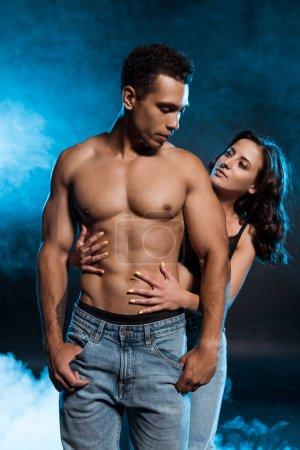 Photo pour Jeune femme sexy étreignant l'homme mélangé musculaire de course sur le noir avec la fumée bleue - image libre de droit