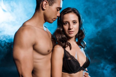 Photo for Shirtless mixed race man near attractive young woman on blue with smoke - Royalty Free Image