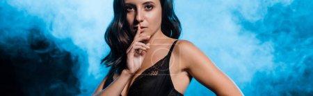 Photo pour Tir panoramique de jeune femme dans le soutien-gorge de dentelle affichant le signe de silence sur le noir avec la fumée - image libre de droit