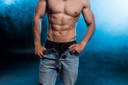 Photo pour Vue recadrée de l'homme musclé touchant jeans en denim sur bleu avec de la fumée - image libre de droit