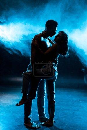 Photo pour Vue latérale de la jeune femme en soutien-gorge en dentelle étreignant sexy musculaire mixte race homme sur bleu avec de la fumée - image libre de droit