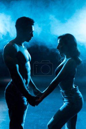 Photo pour Vue latérale de la jeune femme en soutien-gorge tenant la main avec l'homme musclé sexy sur bleu avec de la fumée - image libre de droit
