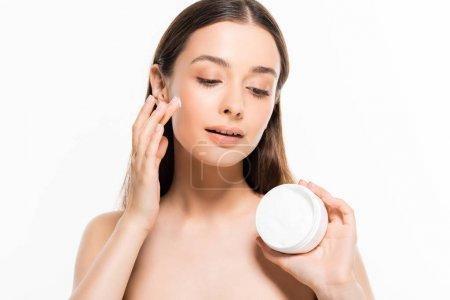 Photo pour Belle jeune femme nue avec la peau parfaite appliquant la crème cosmétique d'isolement sur le blanc - image libre de droit