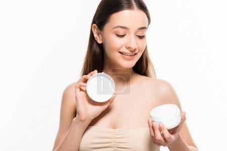 Photo pour Belle jeune femme heureuse avec la peau parfaite regardant la crème cosmétique d'isolement sur le blanc - image libre de droit
