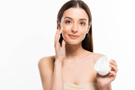 Photo for Beautiful smiling woman with perfect skin applying cosmetic cream on face isolated on white - Royalty Free Image