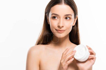 Photo pour Belle jeune femme nue avec la peau parfaite et la crème cosmétique sur le visage regardant loin isolé sur le blanc - image libre de droit