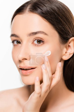 Photo for Beautiful young woman with perfect skin applying cosmetic cream on face isolated on white - Royalty Free Image