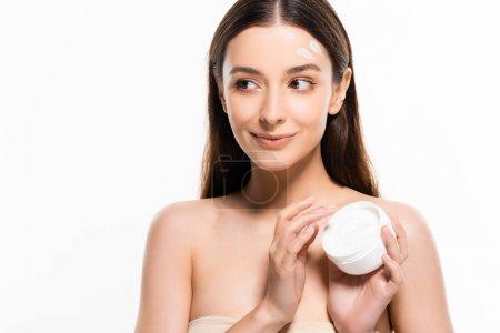 Photo pour Belle jeune femme souriante avec la peau parfaite et la crème cosmétique sur le visage regardant loin isolé sur le blanc - image libre de droit