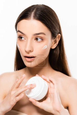 beautiful young surprised woman with perfect skin applying cosmetic cream isolated on white