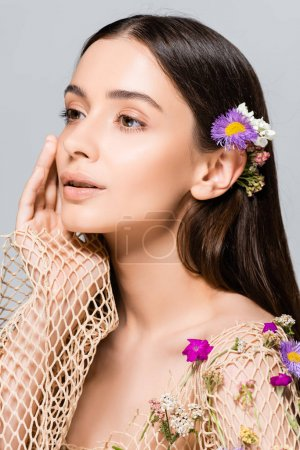 Foto de Hermoso modelo en malla de ropa beige con flores púrpuras tocando la cara aislada en gris - Imagen libre de derechos