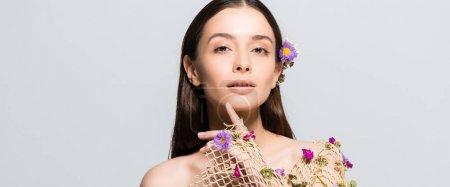 Photo pour Belle femme dans le vêtement beige de maille avec le visage touchant de fleurs pourpres d'isolement sur le gris - image libre de droit