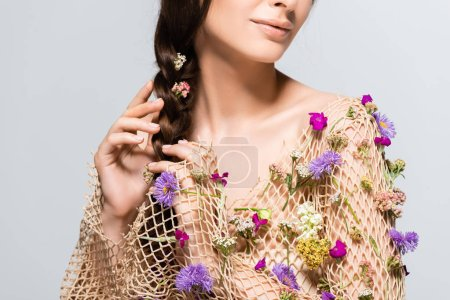 Photo for Partial view of beautiful woman touching braid in mesh with spring wildflowers isolated on grey - Royalty Free Image
