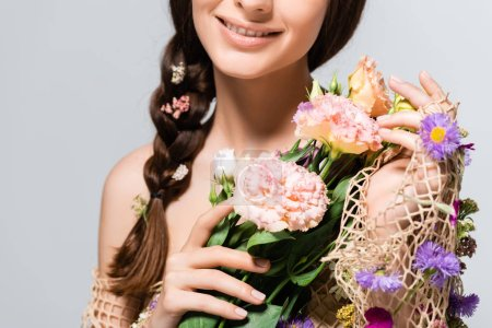 Foto de Partial view of beautiful woman with braid in mesh with spring wildflowers isolated on grey - Imagen libre de derechos